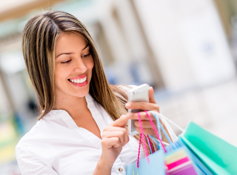 Happy woman using cell phone at a shopping center.jpeg